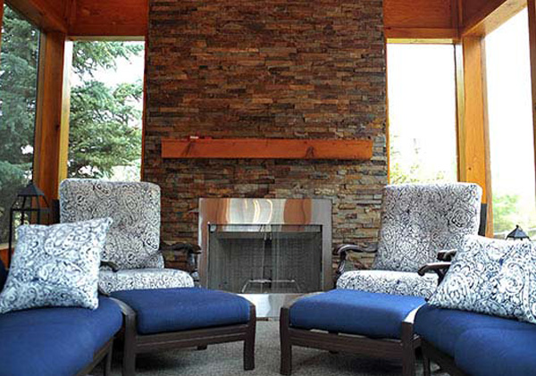 Outdoor stone fireplace constructed in a sunroom.