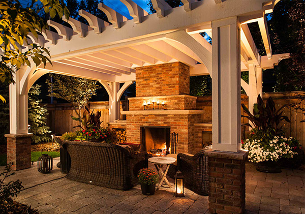 Evening view of the backyard fireplace and patio