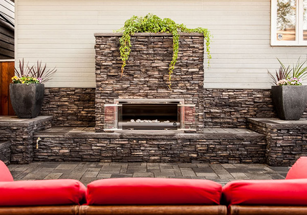 Outdoor fireplace created with stone walls on patio on garage wall.