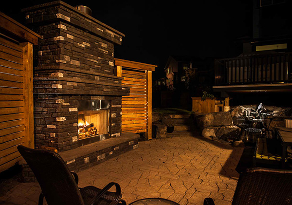 Outdoor fireplace with wood strucure panels to provide privacy and restrict wind.
